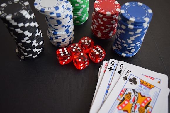 Casino Spiele - Würfel, Chips und Karten auf dem Tisch liegend
